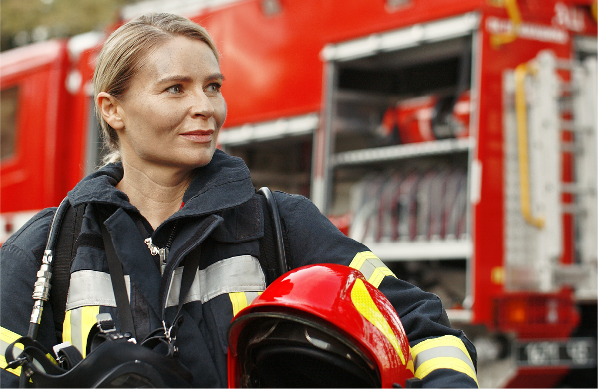 White, blonde female firefighter standing near firetruck