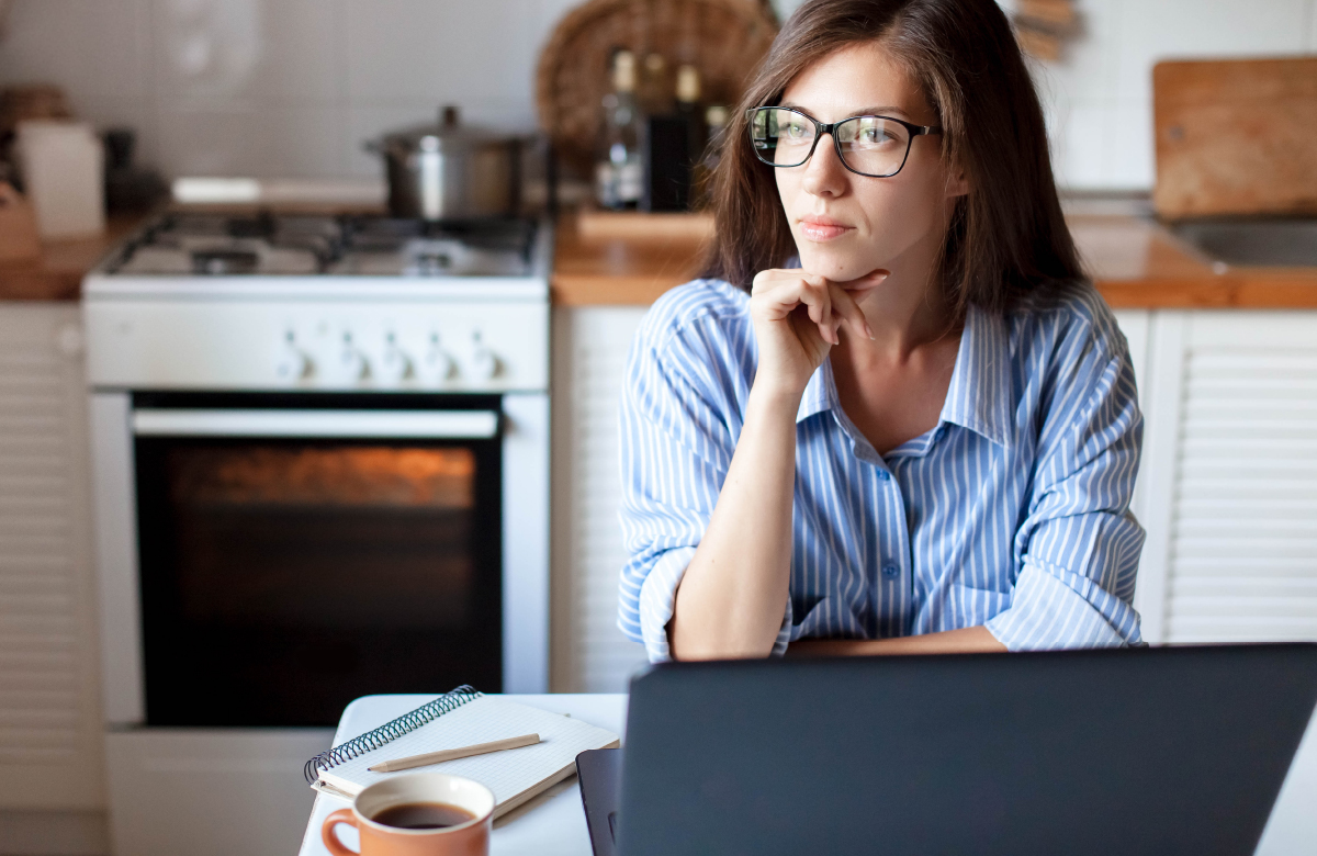 Woman staring into distance while working at kitchen table