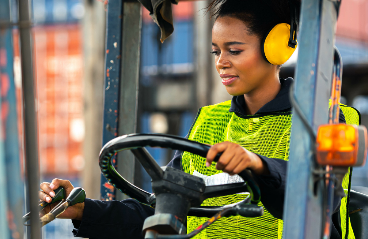 Image of black woman operating forklift in manufacturing environment