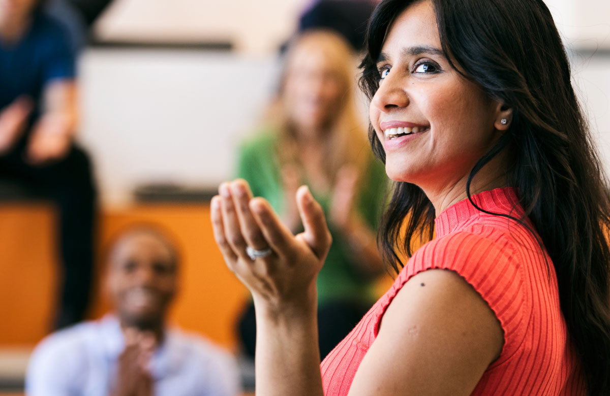 Smiling Latina woman leading positive team meeting