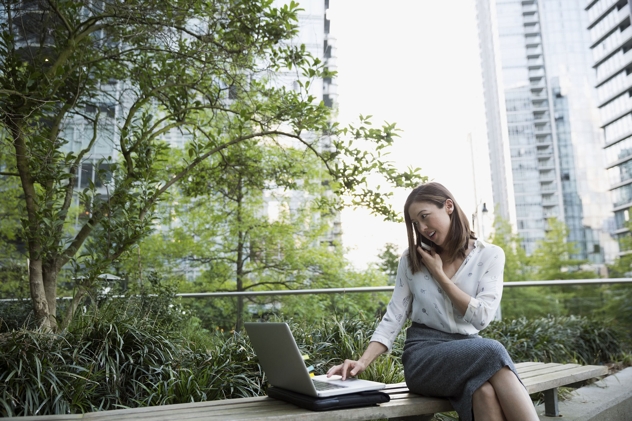 Woman working outside in urban area with phone and laptop
